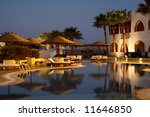 evening illumination in tropical hotel. swimming pool and sunshades - stock photo