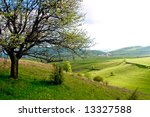Spring landscape with pieces of cultivated farmland and trees - stock photo