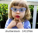 Little girl with glasses, lipstick, necklace and expression playing dress-up - stock photo