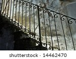 Old italian iron banister with stone stairs and decayed wall - stock photo