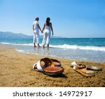Young attractive couple at the beach holding hands (focused front view) - stock photo