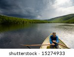 Senior fisherman rowing in a boat on a lake Mikkeljavre in Norway - stock photo
