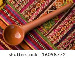 Spoon of clay on tapestry - stock photo