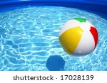 Multicolored beach ball floating on a sparkling blue swimming pool - stock photo