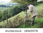 Senior bird watcher using a spotting scope. - stock photo