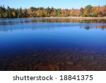 Deep blue lake and Autumn foliage - stock photo