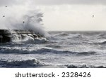 Sea scene with waves crashing against harbor wall - stock photo