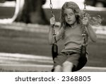 Girl on swing-set in park summertime - stock photo