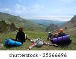 Backpackers relaxing on pass and looking to clouds - stock photo
