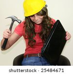 A pretty girl fixes her laptop with a large hammer - stock photo