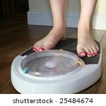 A pair of feet on some scales - stock photo