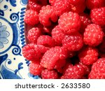 Close up of raspberries on antique plate - stock photo