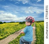 Five year old boy on a bike on a beautiful meadow covered in spring flowers - stock photo