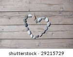 A heart shaped stone on a old wood planks - stock photo