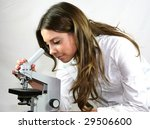 A pretty technician looks down a microscope in a hospital laboratory - stock photo