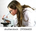 A pretty technician examines a virus under the microscope - stock photo
