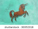 rusty unicorn on green wall - stock photo