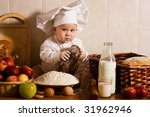 little boy in the cook costume at the kitchen with bread - stock photo