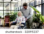 man helping woman in wheelchair - stock photo