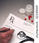 Doctor writing out RX prescription on stainless steel desk - stock photo