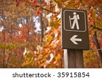 Sign points to a hiking trail in woods in autumn - stock photo