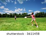 Two little girls playing with a flying disc in a sunny field on a beautiful summer day. - stock photo