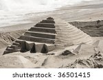 A sandcastle shaped like a pyramid on a beach - stock photo