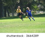 Girls running after a ball playing soccer - stock photo