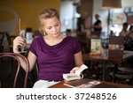 A young beautiful girl with cocktail glass reading book in the coffee house - stock photo