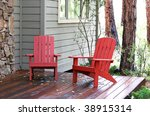 red chairs on front porch in wooded area - stock photo