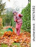 Little girl rake colorful fallen autumn leaves in garden - stock photo