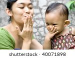 mother teach her baby girl a goodbye kiss - stock photo