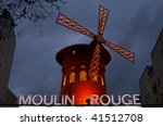 PARIS, FRANCE - DECEMBER 30: The Moulin Rouge by night, shown on December 30, 2007 in Paris, France. The Moulin Rouge is a famous cabaret built in 1889 and located in the Paris' red-light district of Pigalle. - stock photo