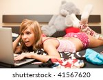 young teen blond woman in bed in chaos of clothes with laptop - stock photo