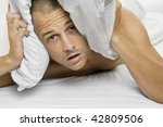 Man trying to sleep with a pillow over his head - stock photo