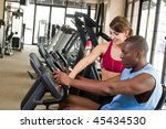 Man and woman exercising together at a fitness center on a stationary bicycle exercise machine.  Woman could be a personal fitness trainer. Focus is on the man in the foreground. - stock photo