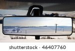 Winter landscape, reflected in the rearviewmirror of a car - stock photo