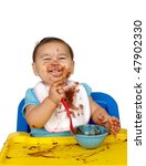 baby girl eating chocolate pudding, messy face, one year old - stock photo