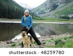Woman standing with dog at lake - stock photo