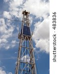 Oil Derrick Against Cloudy Blue Sky - stock photo