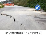 Washed out and damaged road with blue traffic sign pointing direction to attract attention - stock photo