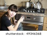 Beautiful housewife switching the oven - stock photo