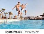 Two men jumping in swimming pool together.  Low angle view from the swimming pool. - stock photo