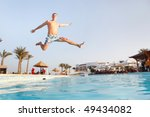Man jumping in swimming pool.  Low angle view from the swimming pool. - stock photo