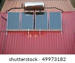Solar powered water heating system mounted on a corrugated metal roof - stock photo