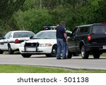 Police roadblock, officer talking to motorist - stock photo