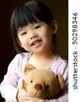 Smiling little child holding a teddy bear in her hand - stock photo