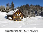 Winter vacation - Rural sunny winter landscape with occupied chalet. - stock photo