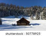 sunny winter landscape with occupied and heated log cabins in the mountains. - stock photo