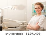 young dental assistant smiling in dentist office - stock photo
